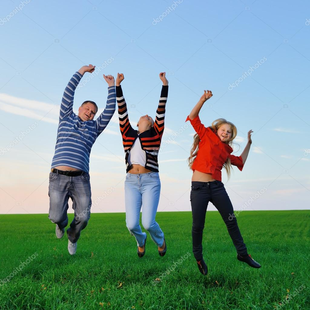 Happy young family jump for joy . The green field and picturesque sky — Stock Photo #13673230