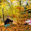Children play yellowing of autumn leaves — Stock Photo #13963554