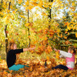 Children play yellowing of autumn leaves — Stock Photo