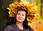 Beautiful woman in the crown of autumn leaves — Stock Photo