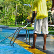 A man cleans the pool — Stock Photo
