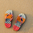 Colorful flip-flops on the sand — Stock Photo