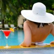 Girl with a cocktail at the edge of the swimming pool — Stock Photo