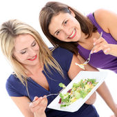 Female friends sharing a plate of salad Female friends sharing a plate of s — Stock Photo