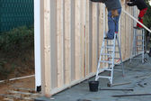 Builders installing a timber frame house — Stock Photo