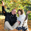Happy couple playing with autumn leaves — Stock Photo