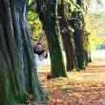 Playful couple peering around an autumn tree — Stock Photo