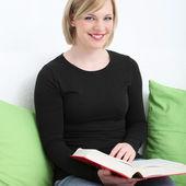 Smiling woman enjoying her book Smiling woman enjoying her book — Stock Photo