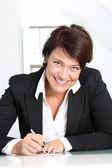 Uśmiechnięta kobieta przy jej biurku — Zdjęcie stockowe