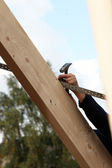 Man nailing a lath to a roof rafter — Stock Photo