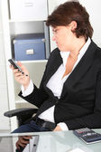 Businesswoman pulling a face at a text message Business woman making a face — Stok fotoğraf