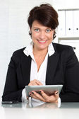 Businesswoman smiling while working — Stock Photo