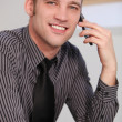a business man talking on his smartphone smiling young man using a smartphone — Stock Photo