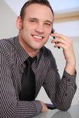 Un homme d'affaires parler sur son smartphone souriant jeune homme à l'aide d'un smartphone — Photo