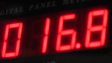 Closeup of a red numerical lcd display on a pressure guage with changing numbers