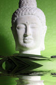 Head of a yoga statue on green background — Stock Photo