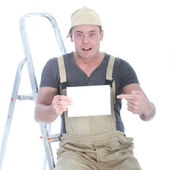 Shocked handyman with blank sign — Stock Photo