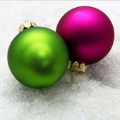 Two Christmas globes, green and violet in the snow — Stock Photo