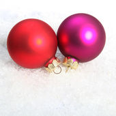 Christmas red and violet globes in snow — Stock Photo