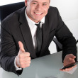 Enthusiastic young businessman showing thumb up — Stock fotografie