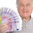 Smiling senior man with a fistful of money — Stock Photo #22039399