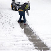Person clearing snow off a pathway — Foto Stock