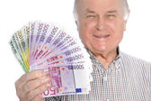 Smiling senior man with a fistful of money — Stock Photo