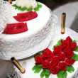 Decorated wedding cake with red roses — Stock Photo