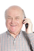 Senior man laughing while talking on phone — Stok fotoğraf
