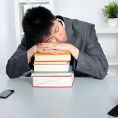 Asian man sleeping on top of a pile of books — Stock Photo