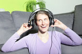 Laughing mature woman listening to music — Stock Photo