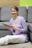 Woman in a living room with a tablet — Stock Photo