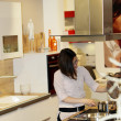 Young housewife cooking in a kitchen — Stock Photo