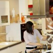 Young housewife cooking in a kitchen — Stock Photo #23588579