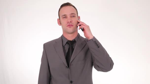 Serio empresario buscando recoger smartphone — Vídeo de stock