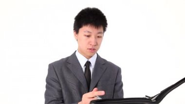 Young Asian businessman writing something — Stock Video