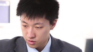 Young asian businessman writes on computer, closeup of head — Stock Video