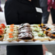 Waiter offering a tray of appetizers — Stockfoto
