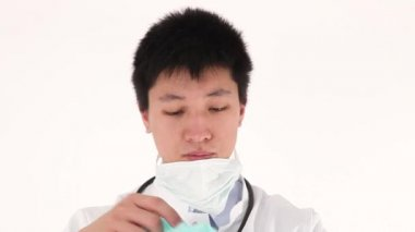 Worried Asian young doctor pulls on protective clothing — Stock Video