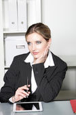 Businesswoman sitting at her desk thinking — Stockfoto
