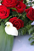 Arum lily in a bridal bouquet of red roses — Stock Photo
