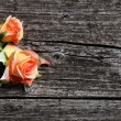 Orange coloured roses on wooden planks — Stock Photo