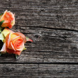 Orange coloured roses on wooden planks — Photo