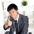 Asian businessman giving a thumbs up — Stock Photo #24455639