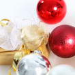 Gold wrapped gift with Christmas baubles — Stock Photo