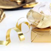Pretty gold wrapped gift and twirled ribbon — Stock Photo