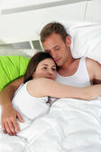 Young couple relaxing together in bed — Stock Photo