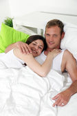 Loving couple resting in bed — Stock Photo