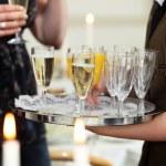 Waiter serving champagne and orange juice — Stock Photo
