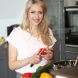 Smiling housewife preparing a meal — Stock Photo